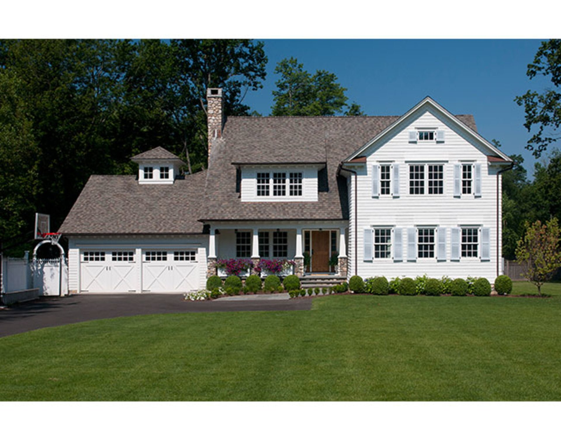 white carriage style garage doors add traditional style to the home